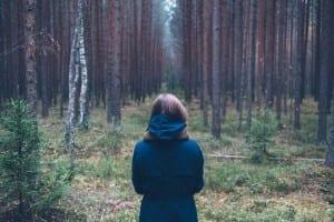 Woman standing in woods.